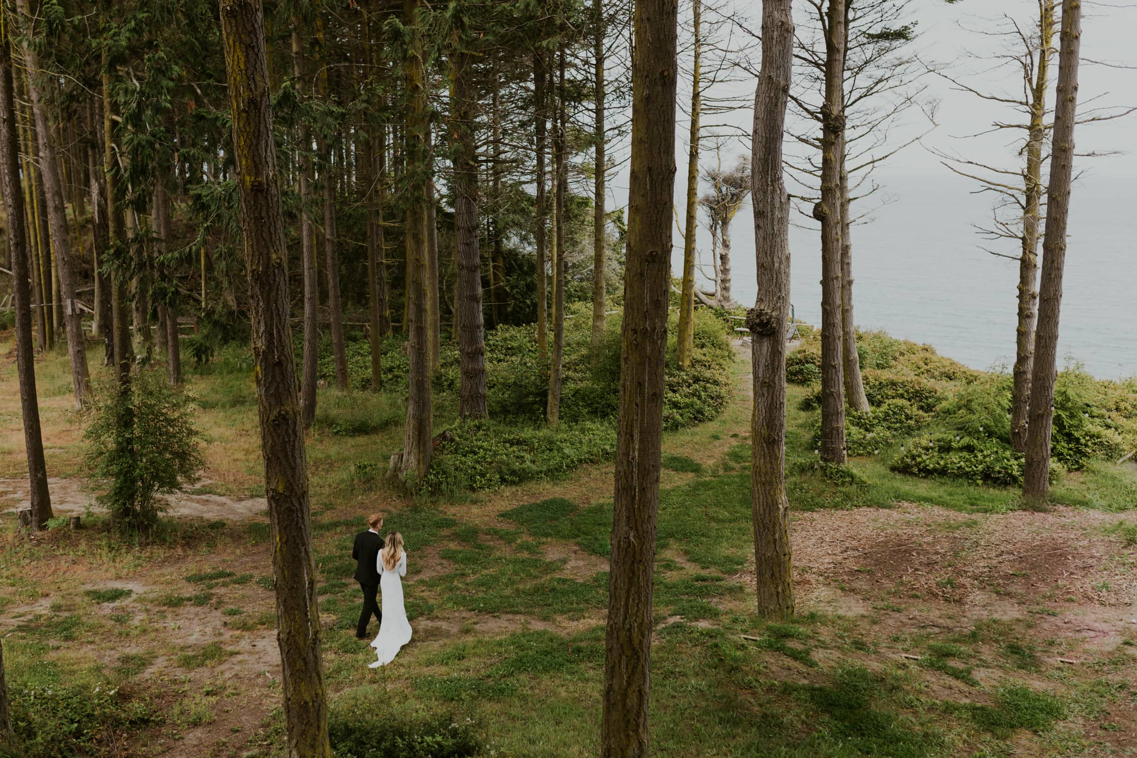 A couple holding hands and walking through trees on their wedding day in Washington State.