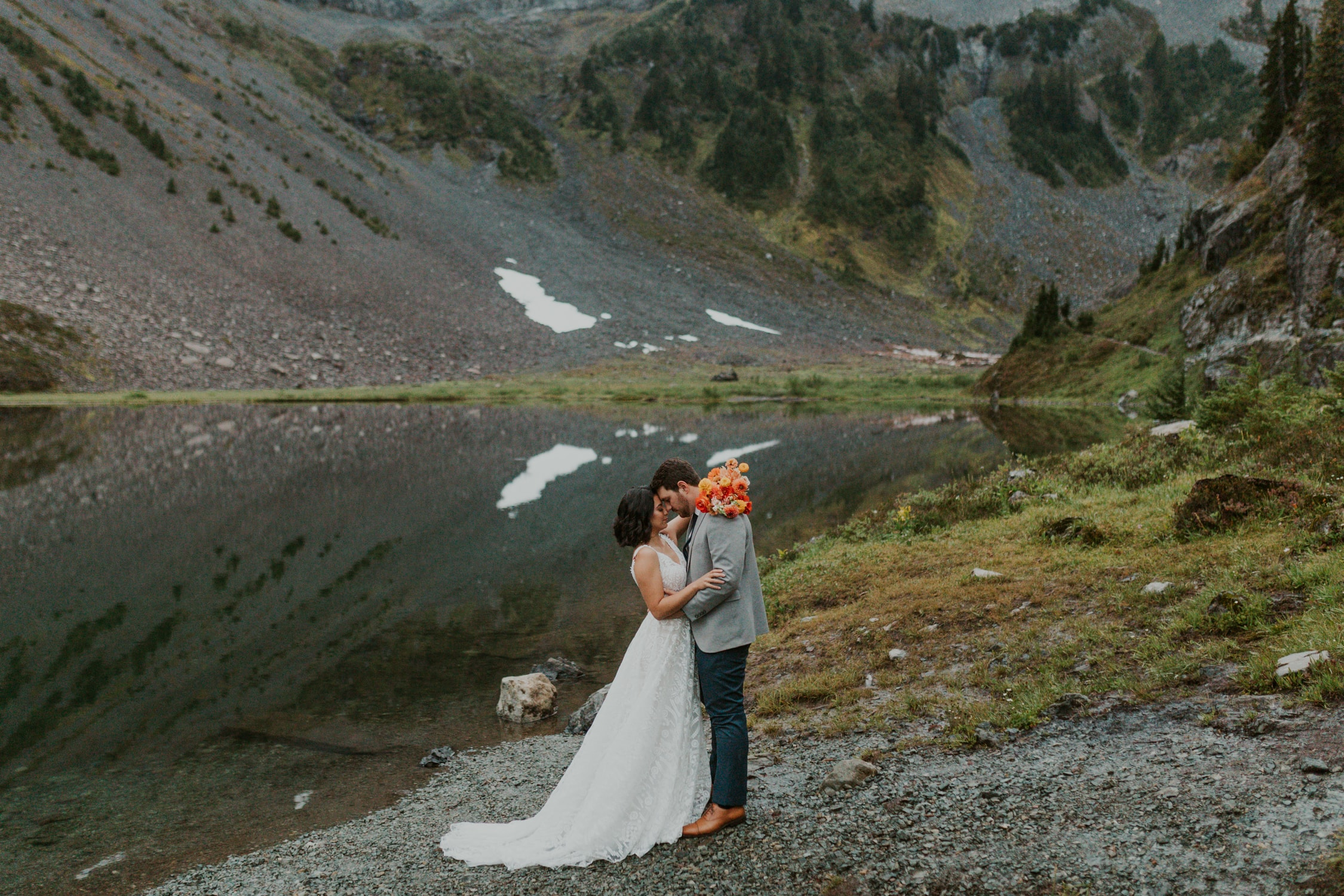 A couple with their foreheads together in front of a lake in North Cascades.