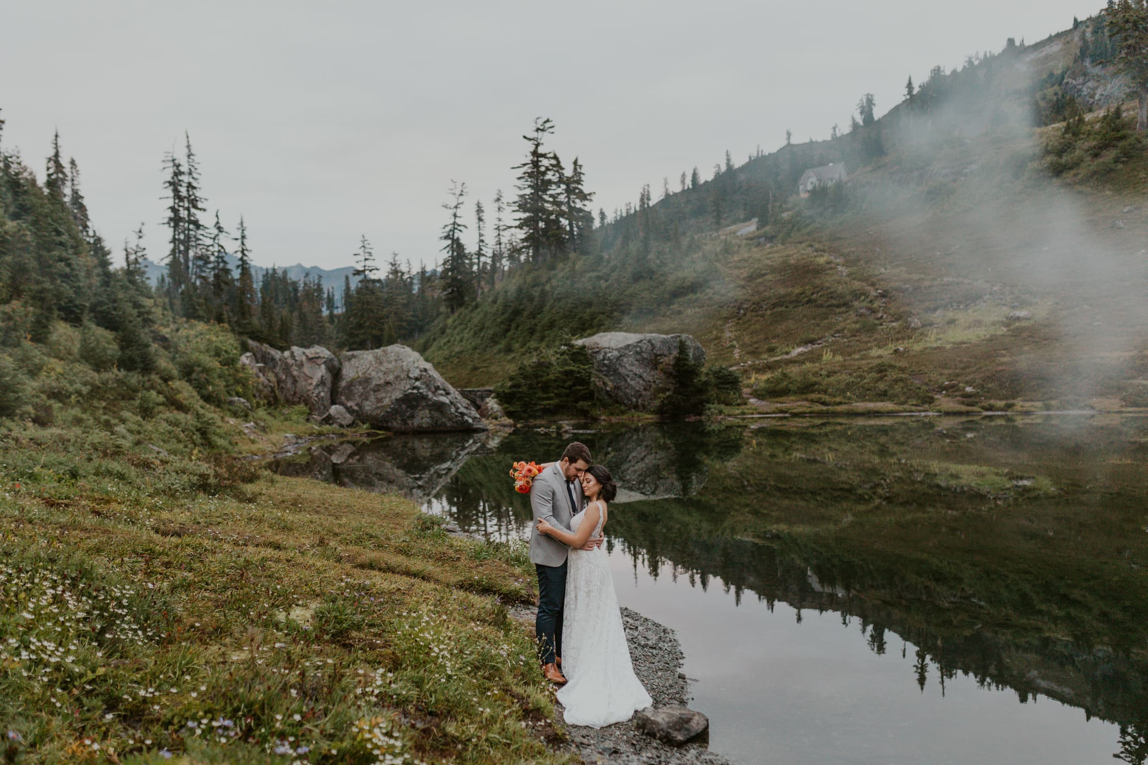 A couple hugging each other in front of a lake in North Cascades.